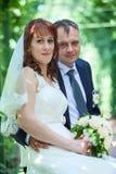 Prepare el abarcamiento de la novia en el vestido blanco cuando siéntese en banco Imágenes de archivo libres de regalías
