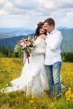 Prepare el abarcamiento de su esposa joven en las montañas r imágenes de archivo libres de regalías