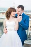 Prepare el abrazo de la novia trasera que va para el beso que se coloca en la terraza con gran paisaje urbano imágenes de archivo libres de regalías