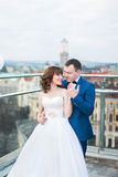 Prepare el abrazo de la novia trasera que va para el beso que se coloca en la terraza con gran paisaje urbano fotos de archivo libres de regalías