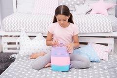 Prepare el bolso para mañana El niño de la muchacha se sienta en cama con el bolso o los cosméticos empaquetan en su dormitorio E imagen de archivo libre de regalías
