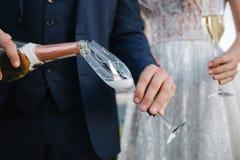 Prepare el champán de colada en un vidrio imágenes de archivo libres de regalías