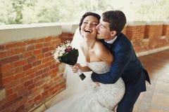 Prepare el cheeck de la novia de las mordeduras que la abraza de detrás imagen de archivo