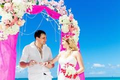 Prepare el donante de un anillo de compromiso a su novia debajo del deco del arco fotografía de archivo