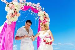 Prepare el donante de un anillo de compromiso a su novia debajo del deco del arco imagenes de archivo