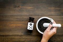 Prepare el veneno Botella con el cráneo y la bandera pirata cerca de la mano que hacen el polvo en mortero en el top de madera os imagen de archivo