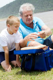 Prepare fishing tackles. Grandfather teaching grandson how to prepare fishing tackles Royalty Free Stock Photography