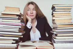 Prepare for an important exam or study a difficult question. Beautiful girl looks up, puzzled, looking out from behind the stacks of books Stock Photos