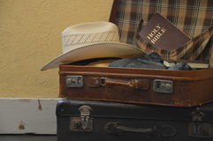 Prepare for a journey. Suitcase filled with clothes, hat and a bible as symbol for travel, journey or a missions trip royalty free stock image