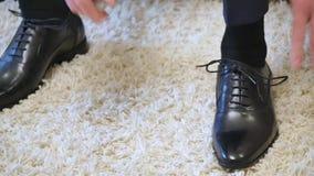 Prepare laços do laço em sapatas pretas em casa antes de visitar a noiva O homem prepara a roupa elegante para a união antes video estoque