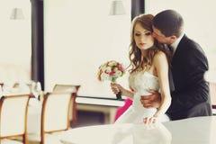 Prepare la cintura de la novia de los controles de detrás blando besando su mejilla imagen de archivo