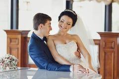Prepare la cintura de la novia de los controles mientras que ella se sienta en sus rodillas foto de archivo libre de regalías