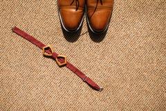 Prepare la corbata de lazo y los zapatos del ` s en el piso imagen de archivo