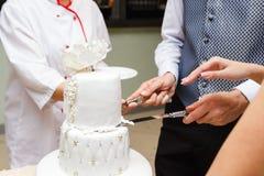 Prepare la mano de la novia de los controles para cortar una torta imagen de archivo libre de regalías