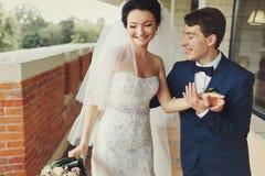 Prepare la mano de la novia de los controles que la lleva a lo largo del balcón fotos de archivo