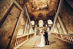 Prepare la mano del ` s de la novia de los controles que se coloca en las escaleras en pasillo pintado imagen de archivo