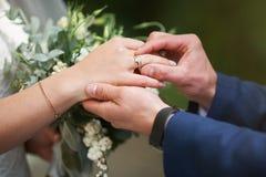 Prepare la mano que pone un anillo de bodas en el finger de la novia fotografía de archivo libre de regalías