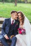 Prepare a la novia con un ramo que abraza y que se sienta en parque foto de archivo libre de regalías