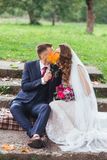 Prepare a la novia con un ramo que abraza y que se sienta en parque imagenes de archivo