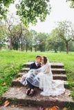 Prepare a la novia con un ramo que abraza y que se sienta en parque fotos de archivo