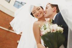 Prepare a la novia de la curva sobre besarla debajo de un velo fotografía de archivo