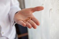 Prepare llevar a cabo dos anillos de bodas en su mano imagen de archivo libre de regalías