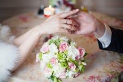 Prepare llevar a cabo las manos de la novia con el anillo de bodas en restaurante imagen de archivo libre de regalías