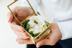 Prepare llevar a cabo los anillos de bodas en caja, los anillos del control del novio, anillo de bodas en mano del novio contrato fotos de archivo