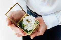 Prepare llevar a cabo los anillos de bodas en caja, los anillos del control del novio, anillo de bodas en mano del novio contrato imagen de archivo