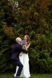 Prepare los cathes una novia mientras que ella se coloca detrás de árboles en parque imagenes de archivo