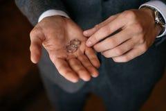 Prepare los controles de sus anillos de bodas de la palma dos foto de archivo libre de regalías