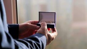 Prepare los controles la caja con los anillos de bodas en su mano y los cierra almacen de metraje de vídeo