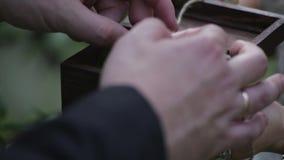 Prepare los controles una caja de regalo de la joyería con los anillos de bodas del oro la mano del ` s del hombre toma el anillo almacen de video