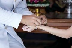 Prepare a los recienes casados que llevan la pulsera del oro en la muñeca del ` s de la novia en ceremonia de boda Fotografía de archivo libre de regalías