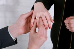 Prepare a mão do ` s que põe uma aliança de casamento sobre o dedo do ` s da noiva casamento foto de stock royalty free