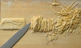Prepare macarronetes home deliciosos, agora apenas corte-os Imagens de Stock Royalty Free