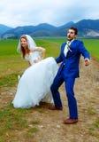 Prepare mirar a escondidas debajo de su vestido de la novia - concepto divertido de la boda fotos de archivo