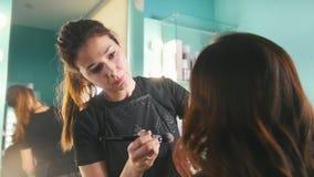 Prepare o processo na loja de beleza para a mulher de cabelo preta nova - fazendo a cara para os olhos video estoque