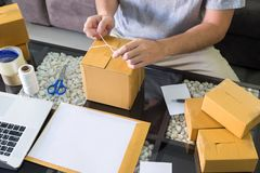 Prepare online shopping parcel Shopping concept, Young start up small business owner packaging cardboard box for sending customer royalty free stock photo