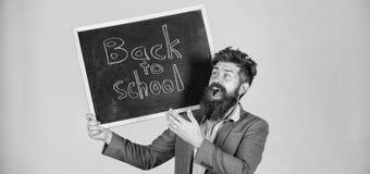 Prepare pelo ano escolar novo O homem farpado do professor est? e guarda a inscri??o do quadro-negro de volta ao fundo do cinza d foto de stock