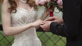 Prepare puesto el anillo de bodas en la mano del ` s de la novia metrajes