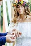 Prepare puesto un anillo al finger del ` s de la novia durante ceremonia de boda imagenes de archivo