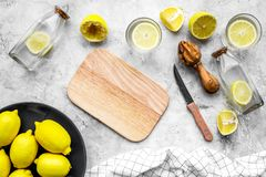 Prepare refreshing beverage lemonade. Lemons, juicer, bottle, knife, cutting board on grey stone background top view Stock Images