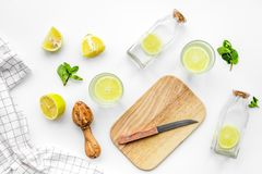 Prepare refreshing beverage lemonade. Lemons, juicer, bottle, knife, cutting board on white background top view Royalty Free Stock Images