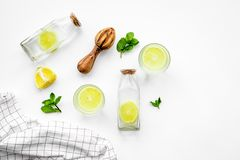 Prepare refreshing beverage lemonade. Lemons, juicer, bottle on white background top view copyspace Stock Photography