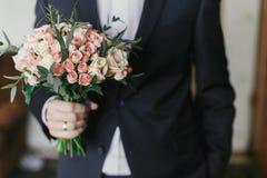 Prepare sostener el ramo elegante con las rosas y el eucalipto Mañana foto de archivo