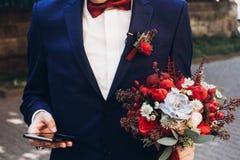 Prepare sostener el teléfono y el ramo con las rosas rojas y los succulents adentro foto de archivo