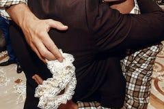 Prepare sostener la liga de seda de la novia en el banquete de boda tradición imagenes de archivo