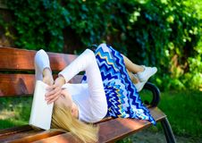 Prepare for test. Woman tired face take break relaxing in garden reading book. Lady student read boring literature. Outdoors. Girl lay bench relax with book royalty free stock images