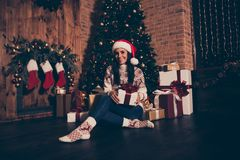 Prepare to Christmastime party. Full length, legs, body, size po. Rtrait of sweet lady in jeans, ornament sweater, socks hold big package sit on floor in living stock photo